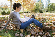 Smiling mother playing with toddler at park during autumn - CAVF20029