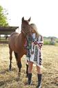 Rancher stroking horse on farm against clear sky - CAVF20086