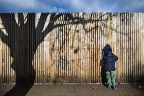 Rear view of boy in warm clothing standing by wooden fence during sunny day - CAVF20167