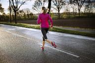 Female athlete running on road during sunset - CAVF20224