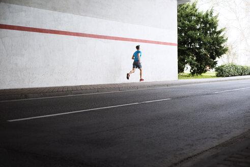 Rear view of male athlete running on sidewalk by road - CAVF20263