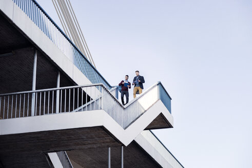 Low angle view of men walking on steps by bridge against clear sky - CAVF20308