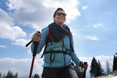 Happy female hiker walking on mountain against cloudy sky - CAVF20320