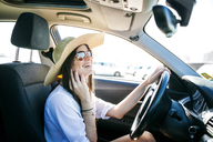 Side view of happy young woman talking on phone while sitting in car - CAVF20362