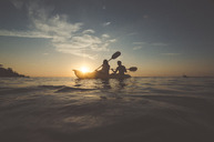 Silhouette friends sitting in kayak on sea against sky during sunset - CAVF20380