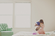 Girl playing with teddy bear in bedroom at home - CAVF20464