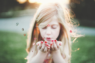 Cute girl blowing heart shapes at park - CAVF20473