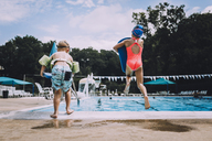 Rear view of siblings jumping into swimming pool - CAVF20506