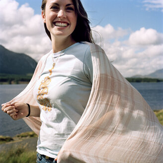 Cheerful woman holding scarf while standing on lakeshore against cloudy sky - CAVF20737