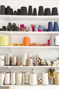 Colorful spools arranged on shelves at home - CAVF20854