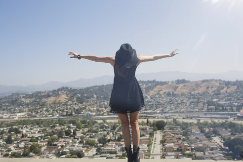 Young woman balancing on retaining wall with city in background against clear sky - CAVF20860