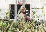 Portrait of farmer holding spring onions in farm - CAVF20923