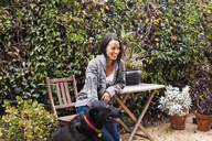 Smiling woman sitting on chair by Labrador Retriever at backyard - CAVF20974