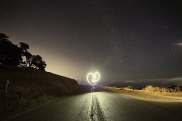 Person making heart shape while performing light painting on mountain road at night - CAVF21220