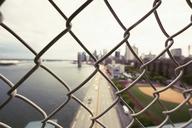 City and Brooklyn Bridge seen through chainlink fence - CAVF21241