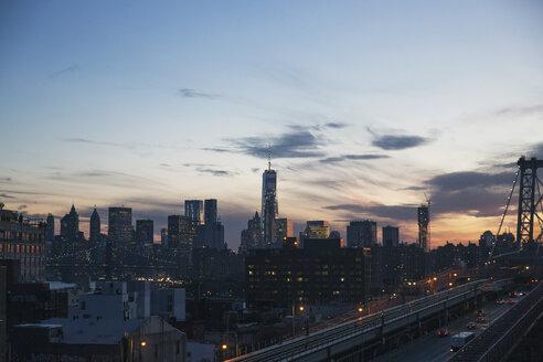 Illuminated city skyline against sky at dusk - CAVF21328