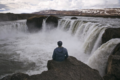 Rear view of man sitting on cliff at Godafoss waterfall - CAVF21376