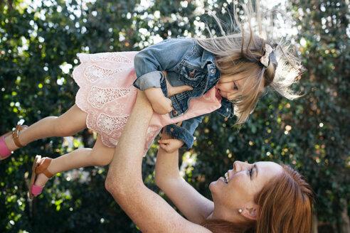 Cheerful mother lifting girl at backyard - CAVF21394