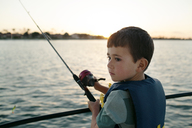 Boy looking away while fishing on boat - CAVF21430