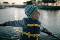 Boy looking away while standing by railing on boat - CAVF21436