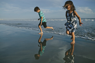 Playful siblings jumping at beach against sky - CAVF21472