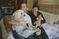 Happy parents carrying baby girl and dog while sitting on bed at home - CAVF21493