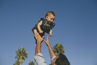 Low angle view of playful father throwing daughter in air against clear blue sky - CAVF21559