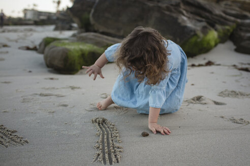 Playful girl playing with sand at beach - CAVF21760