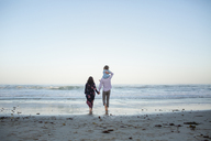 Rear view of man piggybacking daughter while holding woman's hand on shore at beach against clear sky - CAVF21763