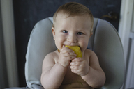 Portrait of shirtless baby boy eating mango while sitting on high chair at home - CAVF21781