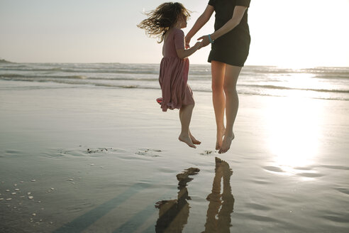 Mother and daughter holding hands while jumping at beach against clear sky - CAVF21793