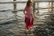 High angle view of girl holding wet dress while standing in water at beach - CAVF21799