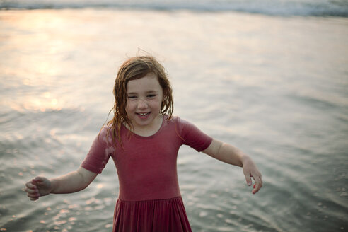 High angle view of happy girl standing in water at beach - CAVF21805