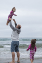 Daughter looking at playful father throwing sister in air while standing on shore against sky - CAVF21817
