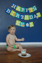 Shirtless baby boy sitting on floor against birthday banner hanging on wall at home - CAVF21829