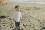High angle portrait of cute boy standing at beach during sunny day - CAVF21883