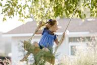 Happy girl swinging on rope swing at front yard - CAVF21898