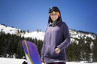 Portrait of smiling woman with snowboard standing on mountains against sky - CAVF21979