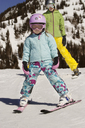Full length of girl and mother with skis standing on snow covered mountain - CAVF22009