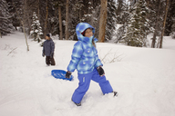 Happy siblings playing on snow covered field against trees - CAVF22012