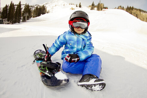 Girl wearing ski goggles sitting by snowboard on snow covered field - CAVF22021