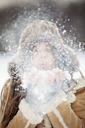 Close-up of woman wearing warm clothing while blowing snow - CAVF22081