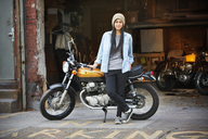 Portrait of female standing with bike outside auto repair shop - CAVF22087
