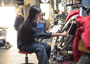 Side view of woman holding digital tablet while repairing bike in workshop - CAVF22099