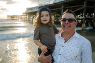 Portrait of father and son at beach during sunset - CAVF22153