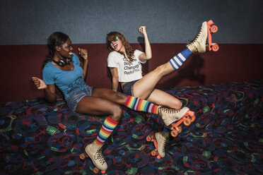 Happy friends wearing roller skates enjoying on sofa - CAVF22276