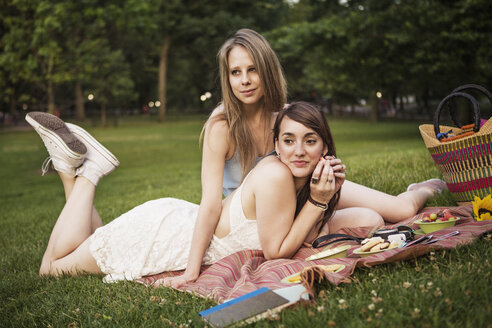 Lesbian couple relaxing on grassy field at park - CAVF22300