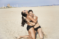Happy female friends embracing while kneeling on sand at beach - CAVF22306