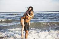 Couple enjoying piggyback ride at shore against sea - CAVF22318