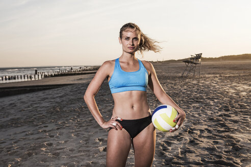 Confident woman holding volleyball and standing at beach - CAVF22324